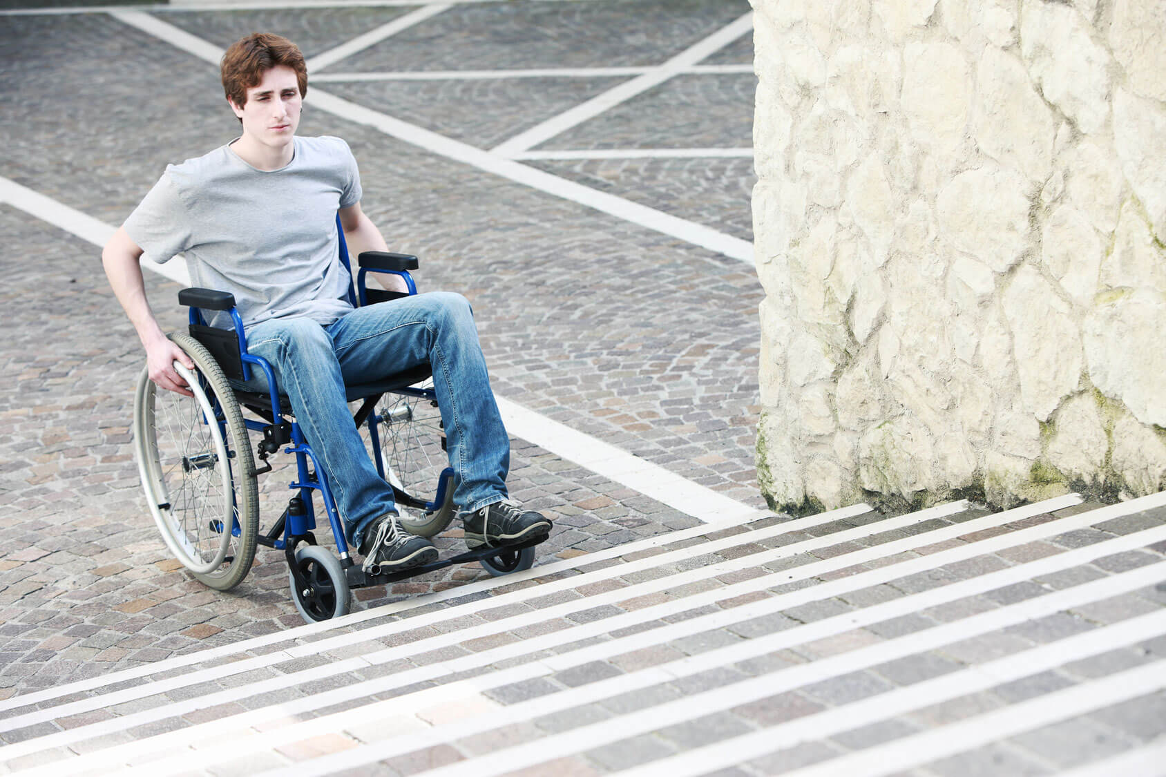 A man with quadriplegia is stuck at the bottom of the stairs because a lack of accessibility